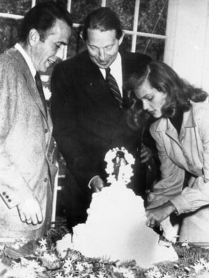 Novelist Louis Bromfield, center, helps actor Humphrey Bogart and his bride, actress Lauren Bacall, cut the cake after their wedding at Bromfield's Malabar Farm, near Lucas, on May 21, 1945. AP file photo Novelist Louis Bromfield, centre, helps actor Humphrey Bogart and his bride, actress Lauren Bacall, cut the cake after their wedding at Bromfield's Malabar Farm, near Lucas, OH, May 21, 1945  (AP Photo)