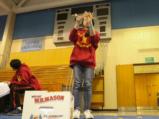 Nicole Zou, an eighth-grader at Hillsborough Middle School, works on building an elastic launch glider plane during Tuesday's competition in the New Jersey Science Olympiad at the Middlesex County College in Edison.