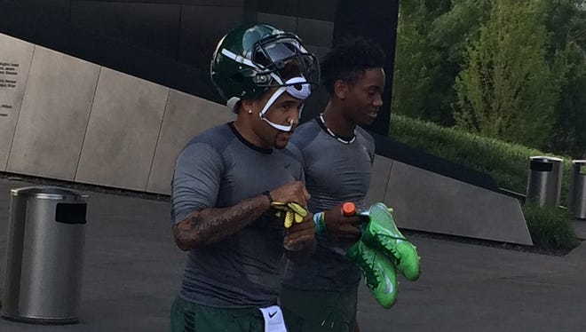 Oregon senior quarterback Vernon Adams (left) leaves practice with freshman quarterback Travis Jonsen.