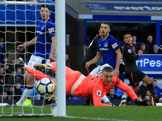 Arsenal's Alexis Sanchez, right, scores his side's fifth goal against Everton during the English Premier League soccer match at the Goodison Park, Liverpool, England, Sunday Oct. 22, 2017. (Peter Byrne/PA via AP)