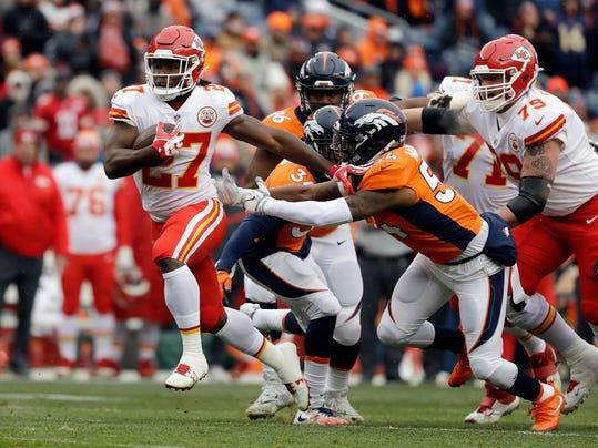 Kansas City Chiefs running back Kareem Hunt (27) runs for a touchdown past Denver Broncos inside linebacker Brandon Marshall during the first half of an NFL football game Sunday, Dec. 31, 2017, in Denver. (AP Photo/Jack Dempsey)