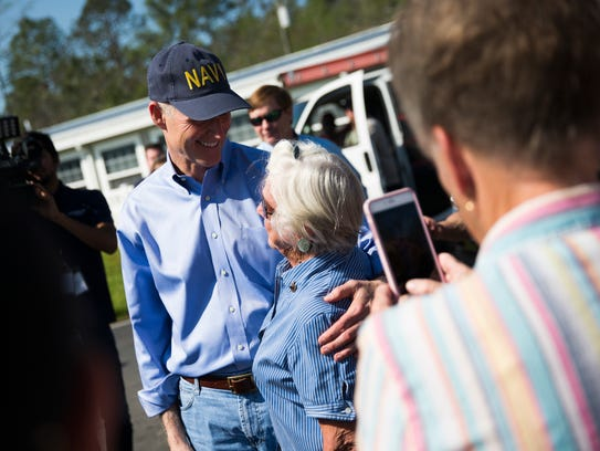 "Gov. Rick Scott looks at Lue ""Mama Lue"" Hewett, 92, a resident of the Club Naples RV Resort during his tour Friday, March 10, 2017, of areas affected by a brush fire. The wildfire was 65 percent contained on 7,500 acres the morning of March 10. Hewett, who has spent 32 winters in the resort, thanked Scott."