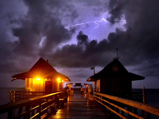 An early morning shower in 2008 off the coast of Naples provides a lightning show for fisherman on Naples Pier.