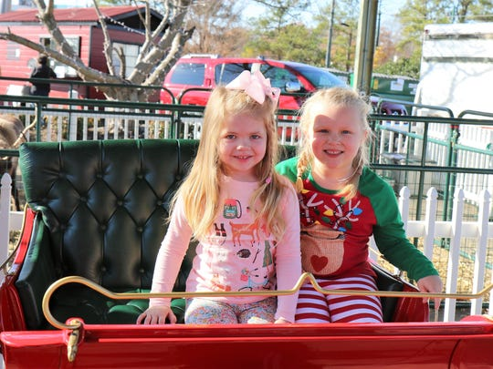 Layla Houston and Isabella Brock pose for a photo on Santa's sleigh with the reindeer looking on during Christmas in the City Dec. 2 at the West Tennessee Farmers Market in downtown Jackson.