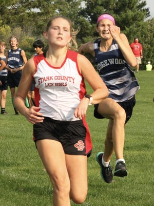 Stark County's Paige Rewerts holds off a late charge from Ridgewood's Kira Messerly in a race for seventh place on Wednesday at The Dunes.