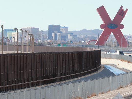 "Traffic moves on the El Paso Border Highway, right, next to the border fence which separates the U.S. and Mexico. The El Paso skyline is in the background. The ""X"" monument at right is in Juárez."