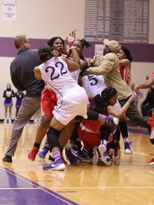 Placers from Ben Davis and Pike fight in the fourth quarter of the game as fans and players spilled on to the court