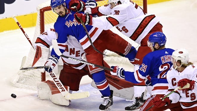 The New York Rangers' Chris Kreider (20) is hit by the Carolina Hurricanes' Brady Skjei (76)  during the first period of a playoff game in Toronto on Tuesday, Aug. 4, 2020. The Hurricanes have revamped their defense since getting swept by the Boston Bruins in last year's Eastern Conference Final, trading for Skjei and Sami Vatanen at the NHL deadline to replace injured defenders Dougie Hamilton and Brett Pesce.