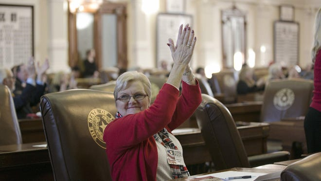 At December 2016 meeting of Texas members of Electoral College, voter Mary Lou Erben applauds announcement that Texas put Donald Trump past the 270 votes needed to win the presidency.