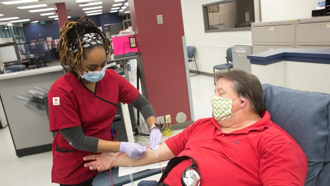 A Red Cross blood donor gives blood during the COVID-19 outbreak at the Mount Hope Blood Donation Center in Baltimore, Maryland.