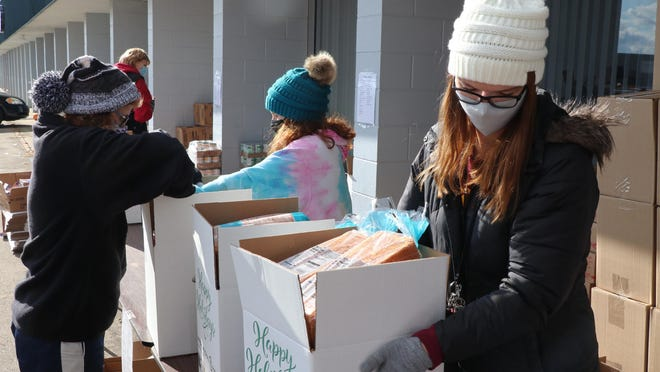 Volunteers from St. Joseph County United Way pack boxes in an assembly-line format Monday as part of a 300-basket Thanksgiving meal distribution. Participants applied for a basket through the local department of health and human services.