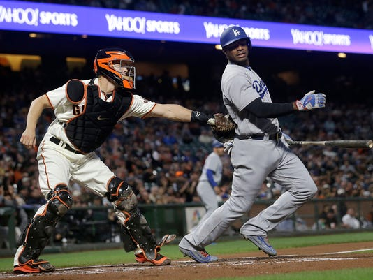Los Angeles Dodgers' Yasiel Puig, right, is tagged by San Francisco Giants catcher Nick Hundley after striking out during the first inning of a baseball game in San Francisco, Tuesday, Sept. 12, 2017. (AP Photo/Jeff Chiu)