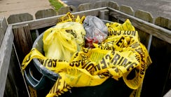 Crime scene tape is in a trash bin along Grandview