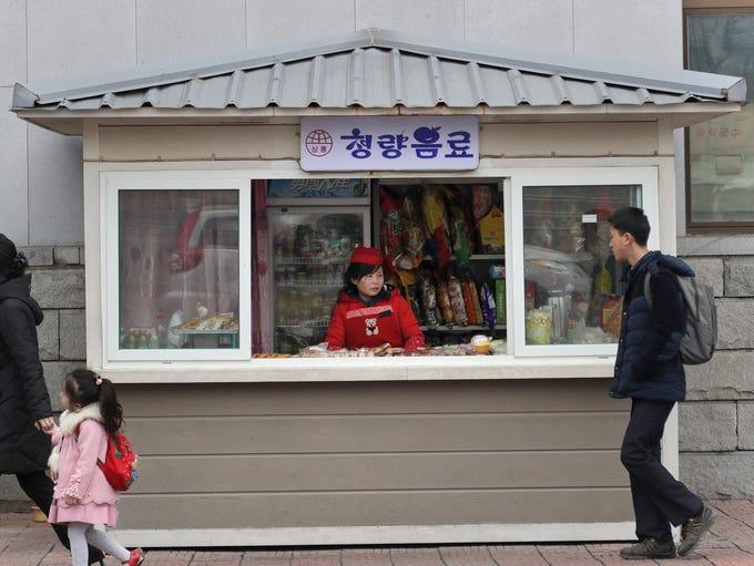 People walk past a kiosk that sells snacks in Pyongyang,