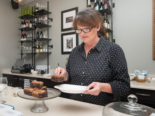 Owner Jo Heckler plates a slice of triple chocolate