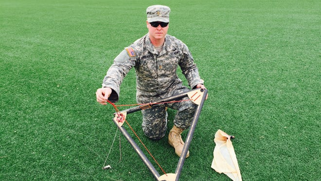 Second Lt. Jordan Henrickson, with 1-36 Infantry, shows his balloon playload and the popped balloon from his latest launch.