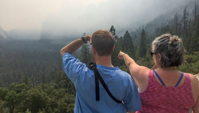 Smoke from the Ferguson Fire blocks some landmarks from the view of visitors Brad Lyons, left, and Courtney Richard at Tunnel View in Yosemite National Park on Tuesday, July 24, 2018.