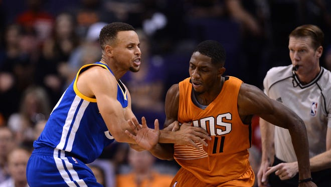 Golden State Warriors guard Stephen Curry (30) pushes and fouls Phoenix Suns guard Brandon Knight (11) away from the ball during the first half at Talking Stick Resort Arena.