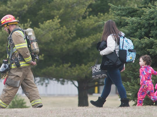Milton firefighters escort people back to their home on Gonyeau Road in Milton on Saturday morning after a gas leak at NG Advantage prompted evacuations of the area.
