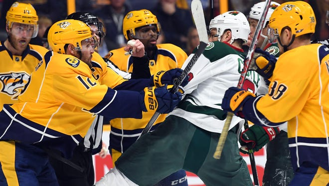 Nashville's Mike Fisher, left, and Minnesota's Charlie Coyle mix it up in December 2016. The Predators have lost three of their first four games against the Wild this season.