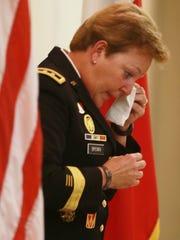 Maj. Gen. Heidi V. Brown wipes away a tear as she speaks
