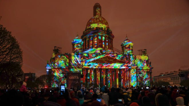 People watch a light show projected on the city's famed St. Isaac's Cathedral during a Festival of light in St.Petersburg, Russia, Friday, Nov. 4, 2016.
