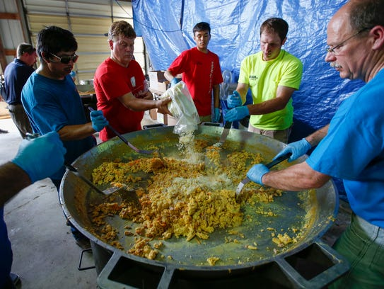 Volunteers work on making large batches of egg, ham