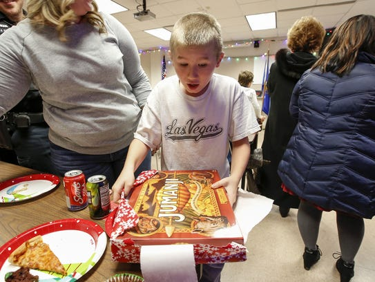 Mark, 11, reacts after unwrapping a gift from the police