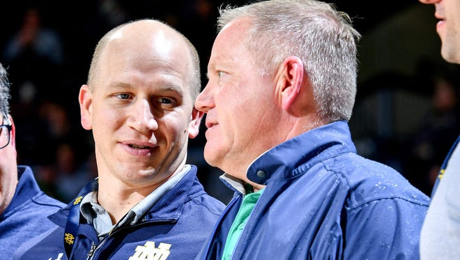 Feb 19, 2018; South Bend, IN, USA; Notre Dame Fighting Irish football defensive coordinator Clark Lea (left) talks with head football coach Brian Kelly as they watch the first half of a basketball game between the Notre Dame Fighting Irish and the Miami Hurricanes at the Purcell Pavilion. Mandatory Credit: Matt Cashore-USA TODAY Sports