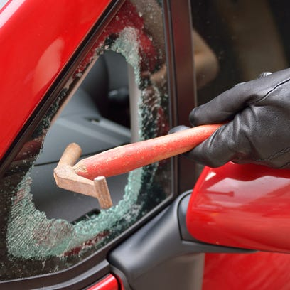 A thief uses a punching tool to smash the window of