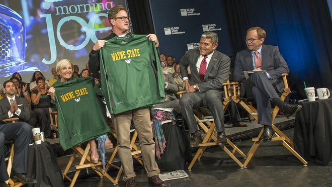 """Mika Brzezinski and Joe Scarborough of MSNBC's """"Morning Joe"""" hold Wayne State University sweatshirts during Thursday's broadcast from the  campus. At right are WSU President  M. Roy Wilson and former U.S. auto task force adviser Steven Rattner."""