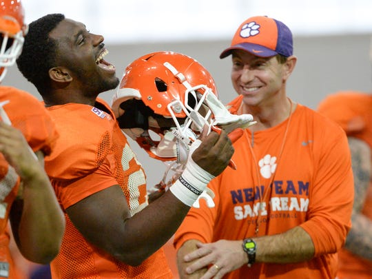 Clemson running back Tavien Feaster (28) and head coach Dabo Swinney laugh together during football practice in Clemson on Wednesday.