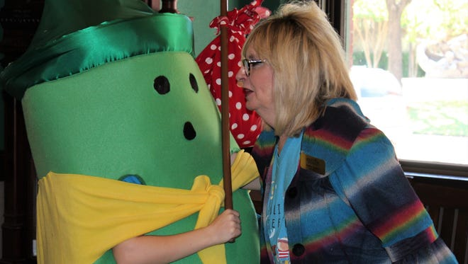 A green crayon seems to react to what Kathy Taylor, part-time director for this year's Children's Art & Literacy Festival, has to say. Perhaps Taylor was telling her storybook friend that lunch during Thursday's Arts Rally at The Grace Museum would include something green - salad.