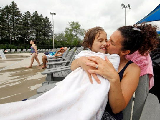 Sue Gronemus, of Wauwatosa, kisses her 8-year-old daughter Cora while the two sit on the deck of the Tosa Pool at Hoyt Park on May 28, 2016.