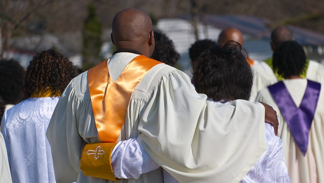 Members of the Friendship House of Prayer Baptist Church sing and march in a procession celebrating the first service in their new space on Easter Sunday, March 27, 2016.