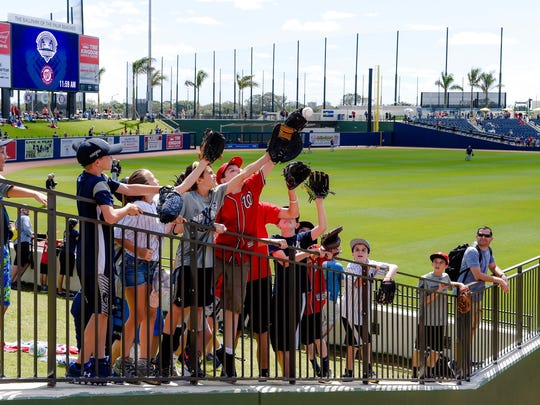 Fans vie for a baseball from the Yankees bullpen before a spring training game against the Nationals at The Ballpark of the Palm Beaches..