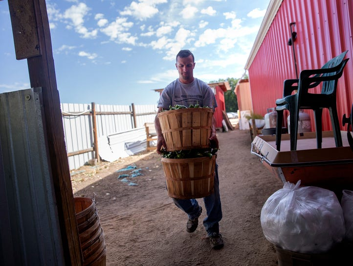 Spivey Vasquez carries green chile to the roasting