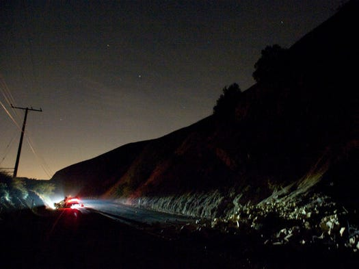 A car sits rolled over near a rockslide, right, in the wake of Friday night's earthquake on Carbon Canyon Road in Brea, Calif.