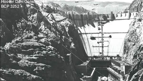 In this U.S. Bureau of Reclamation photo, construction gangs on the Hoover Dam have pushed the past the half-way mark, months ahead of schedule. The foundations for power plants on the Nevada side be seen in the left foreground, and those on the Arizona side in the right foreground. The dark line running up and down the center of the dam is a crack through the entire dam, left temporarily to aid in the cooling of the concrete.