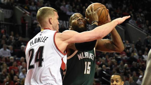 Milwaukee Bucks guard Khris Middleton (22) drives to the basket Portland Trail Blazers center Mason Plumlee (24) during the first quarter of the game at the Moda Center at the Rose Quarter.