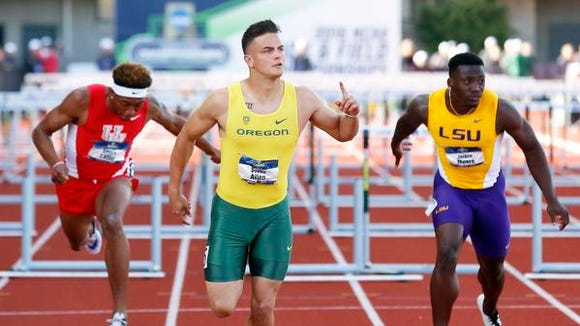 Oregon's Devon Allen, middle, finishes first in the men's 110-meter hurdles at the NCAA outdoor track and field championships in Eugene, Ore., Friday, June 10, 2016. (AP Photo/Ryan Kang)