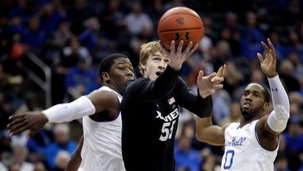 Xavier guard J.P. Macura, center, goes up for a shot against Seton Hall center Angel Delgado, left, and guard Khadeen Carrington, right, during the first half of an NCAA college basketball game, Saturday, Jan. 20, 2018, in Newark, N.J. (AP Photo/Julio Cortez)