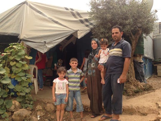 Sihan and Ibrahim stand with their children outside