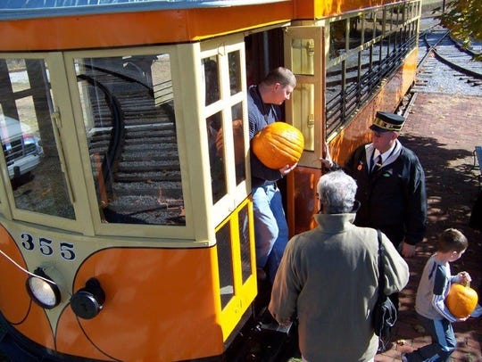 Adults and kids enjoy a ride on an antique trolley.