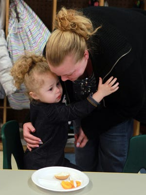 Amber Walker kisses daughter Mya Daniels goodbye as she drops her off at Bright Days Child Development Center in Newport. Because her income was $45 over the limit, Walker's state child care subsidy was cut.