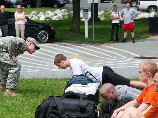 Sgt. Geoffrey Emschweiler with the Pennsylvania Army National Guard calls out a cadet with push ups after he went to the wrong platoon during registration and didn't listen to directions. Parents watch and photograph the last time they will see their teens for the week in the background. YORK DAILY RECORD/SUNDAY NEWS - PAUL KUEHNEL