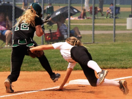 Plymouth third baseman Gina Barber reaches to tag Allen Park baserunner Hailey Genaw (No. 12) during Saturday's Division 1 softball regional final.
