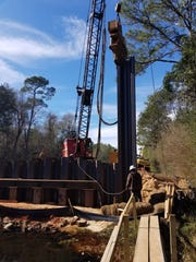 Workers drive pilings into Freeman Springs on Arthur