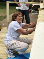 Among a group of volunteers of various skill levels, happy to help, is Therese Poirier of White Lake.