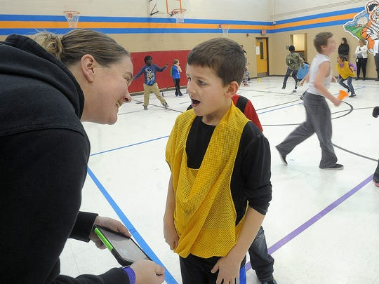 Gretchen Johnson, physical education teacher at Cleveland Elementary School, talks with third grader Lincoln Nagel, who is open enrolled, during class on Dec. 9. Cleveland has 73 open enroll in and 189 going out.